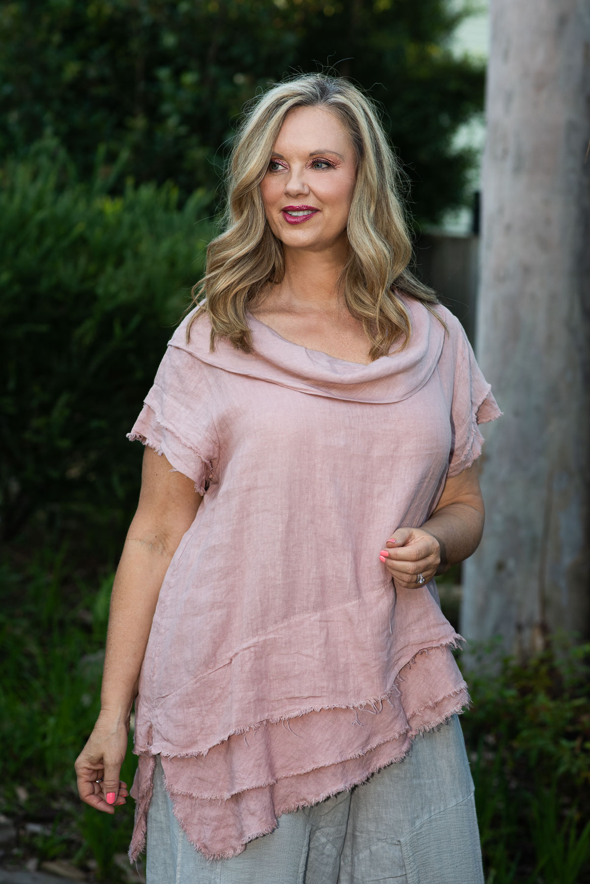 100% Linen clothing this is a short sleeve assymetrical top with a ruffle tier at the bottom and cowl neck